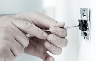 Hand bei Elektroinstallation mit einem Schalter