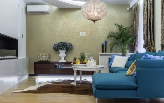 Schön beleuchtetes Wohnzimmer mit blauem Sofa